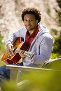 Stock Photo of African American man playing acoustic guitar