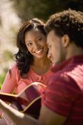 African American man playing guitar for girlfriend - stock photo