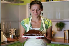 House wife presenting freshly baked chocolate cake - stock footage