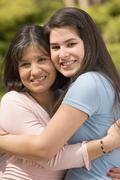 Hispanic mother and daughter hugging - stock photo