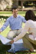 Hispanic couple laying down picnic blanket - stock photo