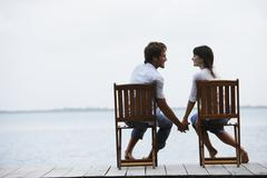South American couple holding hands on dock - stock photo