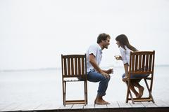 South American couple with wine on dock Stock Photos