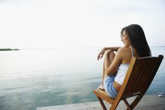South American woman in deck chair on dock - stock photo
