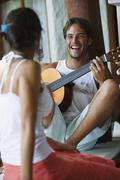 South American man playing guitar for girlfriend Stock Photos