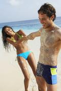 Stock Photo of South American woman pulling boyfriend at beach