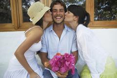 Two women kissing man on both cheeks Stock Photos