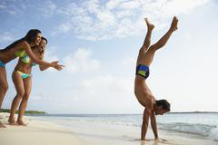 South American man doing handstand on beach - stock photo