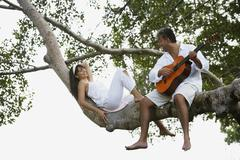 South American man playing guitar for wife Stock Photos