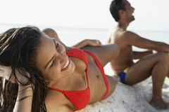 South American couple laying on beach - stock photo