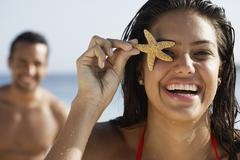 South American woman holding starfish over eye Stock Photos