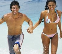 South American couple running in water - stock photo