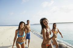 South American friends running at beach Stock Photos