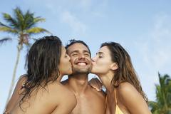 South American women kissing man on both cheeks Stock Photos