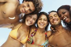 South American friends hugging at beach Stock Photos