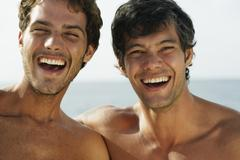South American men laughing at beach Stock Photos
