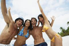 South American friends cheering at beach Stock Photos