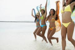 South American women jumping on beach - stock photo