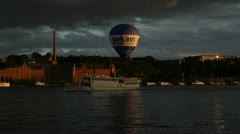 Boat passes under low flying hot air balloon in central Stockholm at dusk Stock Footage