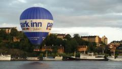 Hot air balloon low over lake in central Stockholm Stock Footage