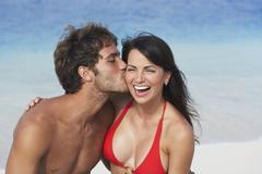 South American man kissing girlfriend's cheek - stock photo