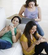 Three young women using wireless devices Stock Photos