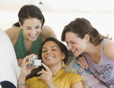 Three young women looking at video camera Stock Photos