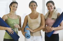 Three young women in yoga class - stock photo