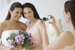 Hispanic bride and bridesmaid being video recorded Stock Photos