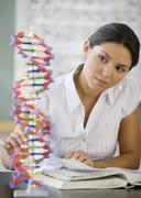 Hispanic woman looking at DNA model - stock photo
