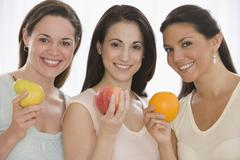 Three young women holding fruit Stock Photos