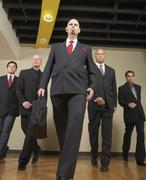 Multi-ethnic businessmen walking in formation - stock photo