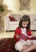 Middle Eastern girl reading on floor Stock Photos
