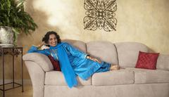 Stock Photo of Indian woman sitting on sofa