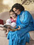 Indian grandmother reading to granddaughter - stock photo