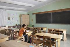 Mixed Race boy in empty classroom Stock Photos