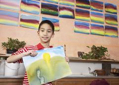 Asian boy holding painting Stock Photos