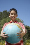 Asian boy holding globe Stock Photos