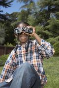 African boy looking through binoculars - stock photo