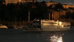 Passenger steamboat cruises in central Stockholm at nightfall Stock Footage