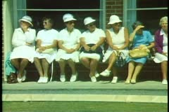 Ladies sitting on a bench at croquette match, Christchurch, New Zealand Stock Footage