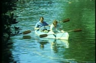 Stock Video Footage of Avon River in Christchurch, New Zealand, canoe rowing down river, wide shot