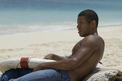 Hispanic man holding life preserver at beach Stock Photos