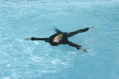 Hispanic businessman in swimming pool Stock Photos