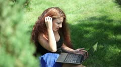 Armenian girl with long hair communicates on the Internet in the park. - stock footage