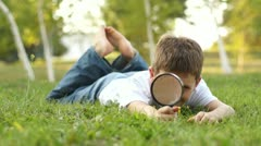 Boy playing with magnifier - stock footage
