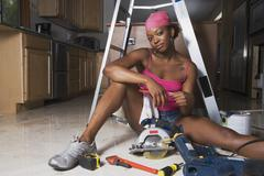African woman on floor with power tools - stock photo