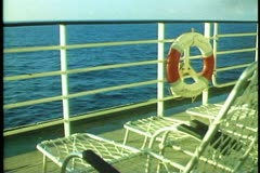 QE2 deck, rail, ring buoy, deck chairs, sea, POV passing Stock Footage
