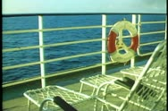 Stock Video Footage of QE2 deck, rail, ring buoy, deck chairs, sea, POV passing
