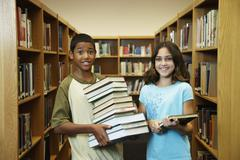 Multi-ethnic students holding library books Stock Photos